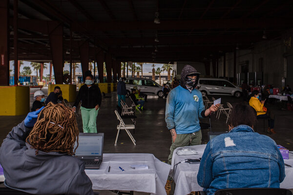 A farmworker checking in with nurses for his vaccination appointment at at a pop-up clinic hosted by Anthony Vineyards in Coachella, Calif.