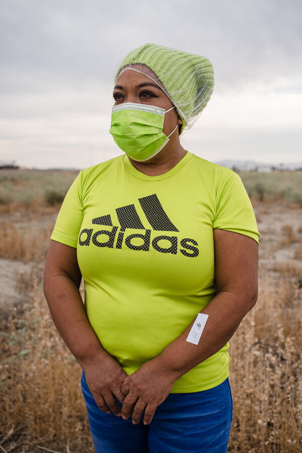 Rosa Torres, a Mexican immigrant, taking a break from packing dates to get vaccinated. The sticker on her arm designates when she got her shot.