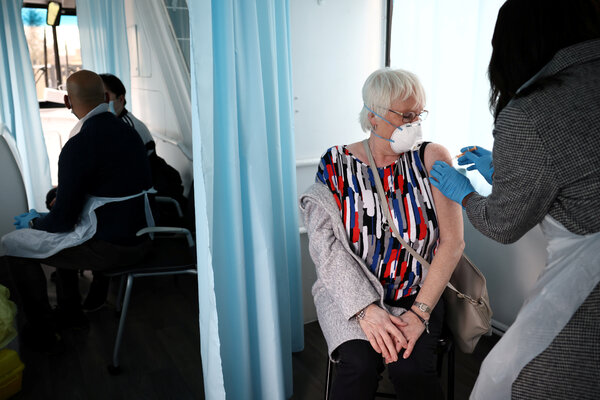 A woman receiving a dose of the Oxford-AstraZeneca vaccine inside a bus modified into a mobile vaccination center in London last month.