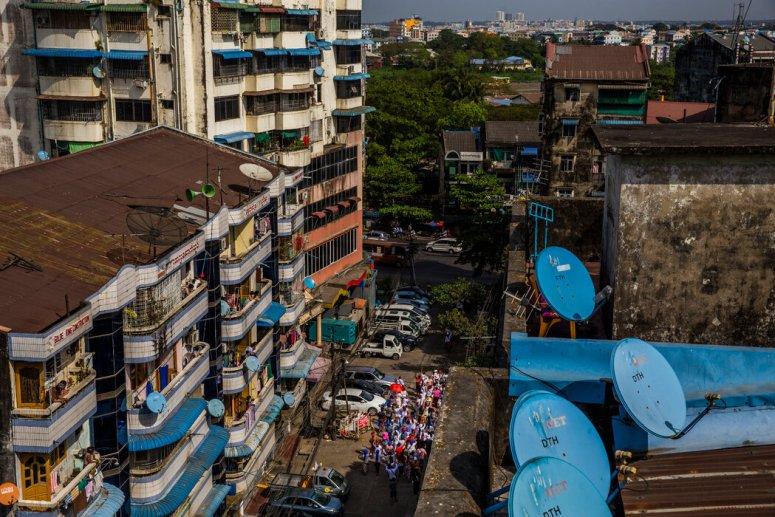 二月的仰光,一群人从自己居住的社区出发前去参加抗议活动。