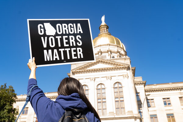 Demonstrators stand outside the Georgia Capitol building to oppose voting restrictions.