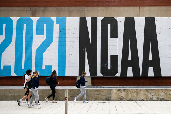 Pedestrians walking past an N.C.A.A. banner in Indianapolis on Sunday.