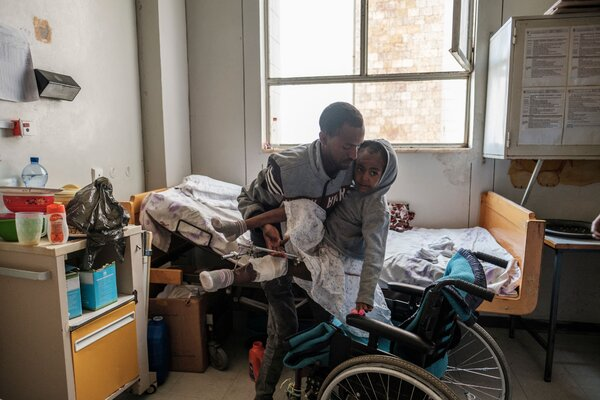 Arsema Berha, 9, being moved into her bed by a relative at Ayder Referral Hospital in the Tigray capital Mekele last month, after being injured during fighting.