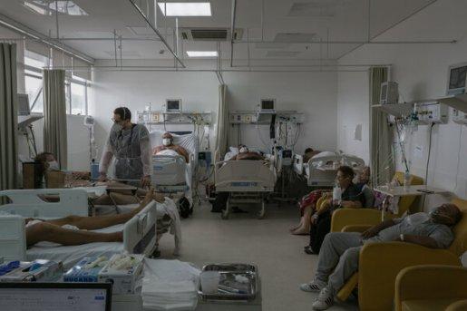 Un trabajador de la salud inspecciona a un paciente en la unidad de cuidados intensivos para pacientes con la COVID-19 en el Hospital Restinga e Extremo Sul.