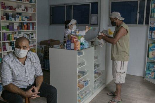 Henrique Machado, a la izquierda, sobrino de Terezinha Backes, fallecido por la COVID-19, en una farmacia de São Leopoldo, municipio de las afueras de Porto Alegre.