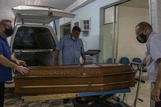 Guaraci Machado, a la derecha, quien se opone a los confinamientos y cierres de negocios relacionados con la pandemia, en su funeraria en São Leopoldo al recibir el ataúd de un hombre que murió a causa de la COVID-19.