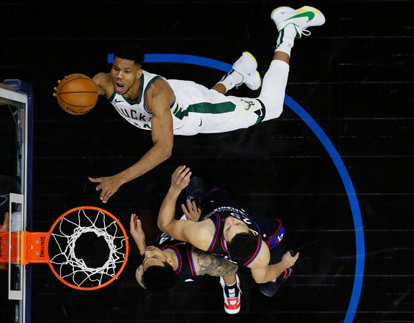 Giannis Antetokounmpo of the Milwaukee Bucks goes for a shot against Ben Simmons and Danny Green of the Philadelphia 76ers.  NBA top shot on digital sports fan