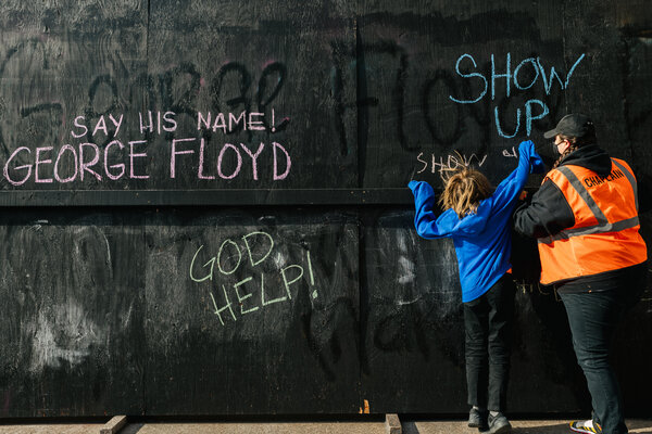 Kelly Sherman-Conroy and her son Ciaran Conroy write on a wall across from the Hennepin County Government Center on Friday.