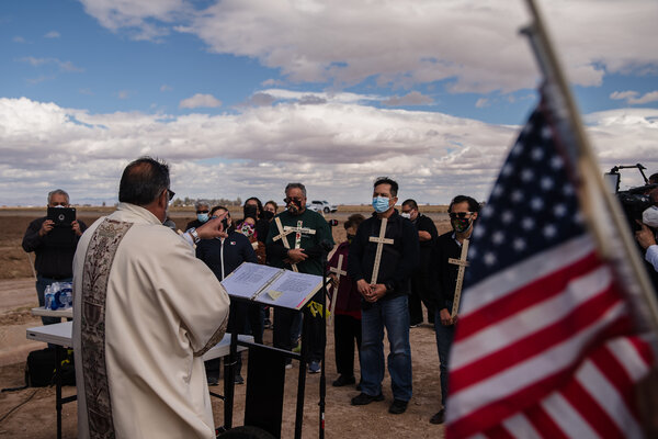 Mourners, clutching crosses with the names of the 13 migrants who lost their lives in the crash, listening to Deacon Marcos Lopez at a vigil near the crash site on March 10.