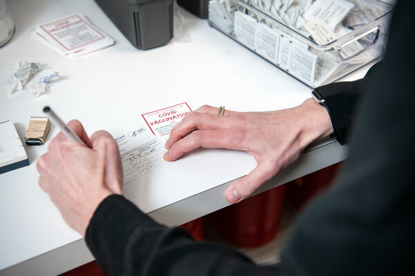 A pharmacist in Little Rock, Ark., filling out a Covid-19 vaccine card last month.