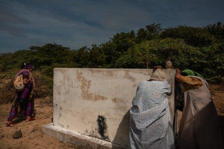 Magaly Báez, al centro, ante la tumba de su hijo