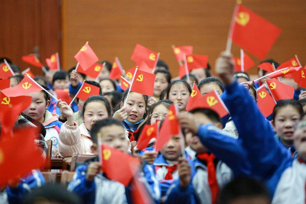 中国扬州,一群学生在一个庆祝建党百年的活动上挥舞党旗,在该活动上,他们观看了《建党伟业》。