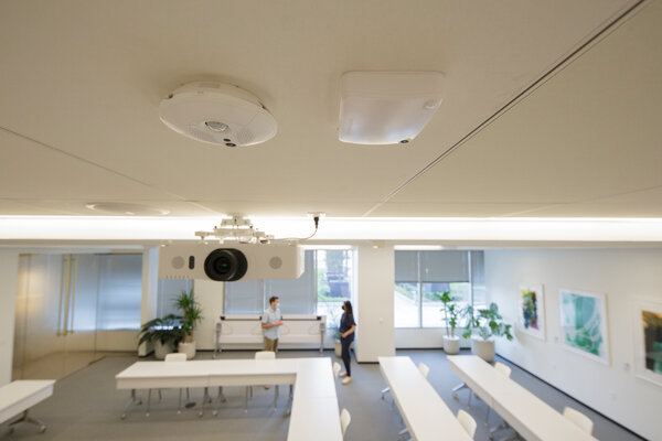 Two occupancy sensors affixed to a ceiling, being tested by the development firm Hines, can track the number of people and their movements in this conference room.