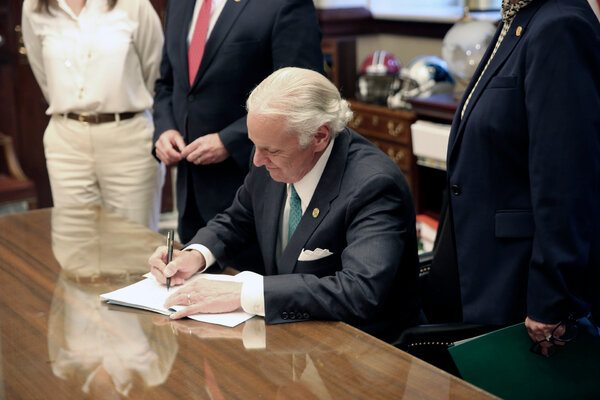 Governor Henry McMaster ofSouth Carolina  signing a bill on April 22 requiring schools to provide in-person classes five days a week starting on April 26, in Columbia, S.C.