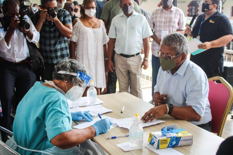 塞舌尔总统瓦韦尔·拉姆卡拉旺(右)今年1月接种第一剂中国国药集团疫苗前填写有关表格。他为本国的疫苗接种计划进行了辩护。