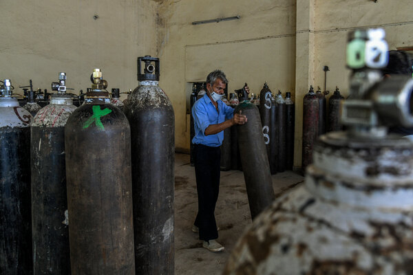 Workers moved oxygen cylinders for transport at a factory in New Delhi on Sunday. The city has now received enough oxygen to share its supply.