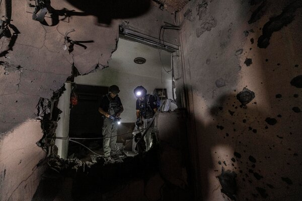 Members of Israeli bomb squad unit inspect the damaged house after it was hit by a rocket fired from the Gaza Strip, in Sderot, Israel, Wednesday.