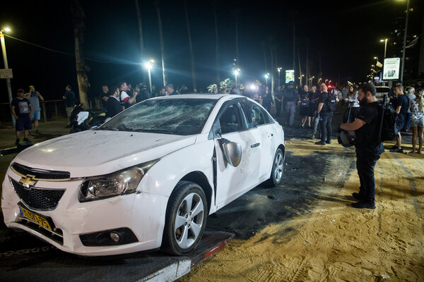 A police officer inspecting the car of an Arab Israeli man whom a Jewish mobinjured in an attack in Bat Yam last week.