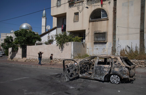 An Israeli Arab woman and her daughter walking past the wreckage of a car in Lod, Israel, on Wednesday.