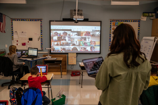 Students participating in a math activity in a first-grade class while their remote classmates were projected on a screen at James Monroe Elementary School in Edison, N.J., in November.