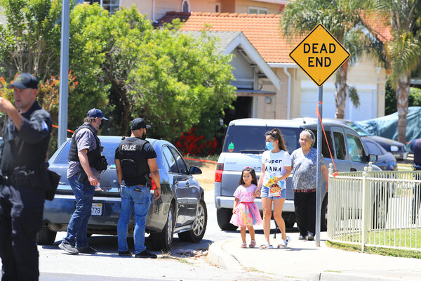 Police officers watched as residents who live near the suspect's home, center, left the area.