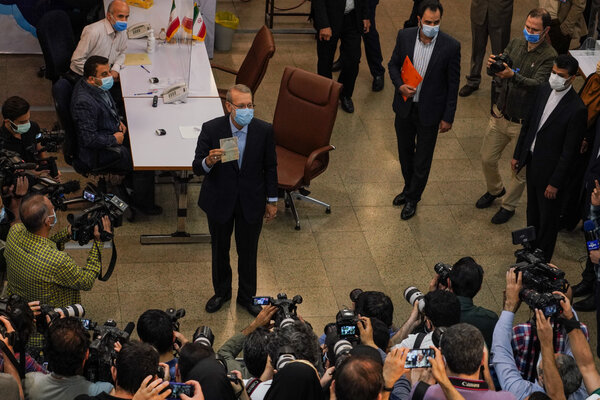 Centrist conservative Ali Larijani, center, registering in Tehran.