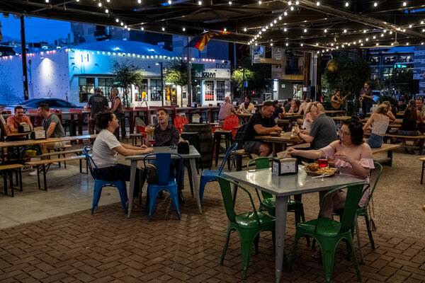 Patrons dined at an outdoor brewery in Phoenix on Thursday. Arizona is among the states that are ending additional federal payments to unemployed workers.