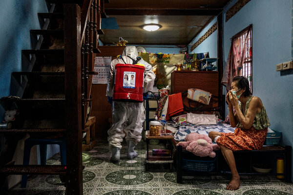 A rescue worker sprayed disinfectant at a home in theKhlong Toey slum in Bangkok, after a resident tested positive for the coronavirus.