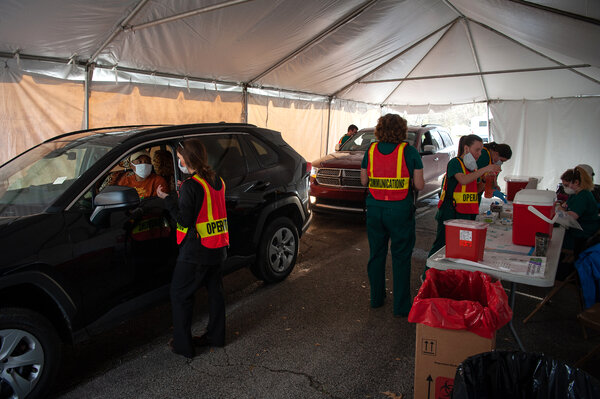 Administrators operating a drive through vaccine site on the campus of Delta State University in Cleveland, Miss., in March.