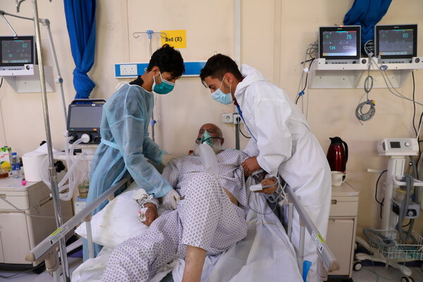 Two men helping their father last month at the Afghan-Japan Communicable Disease Hospital in Kabul, Afghanistan.