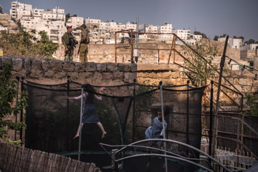 Israeli soldiers standing guard as children play in a Jewish settlement in the West Bank in 2019.