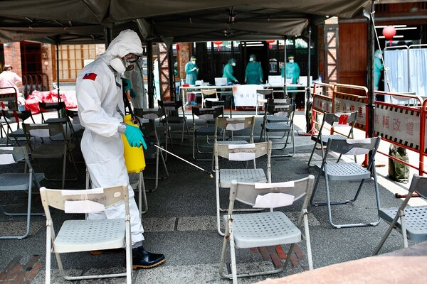 Disinfecting seats at a Covid-19 testing site in Taipei on Saturday.
