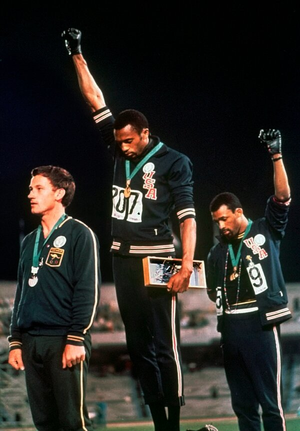 Tommie Smith, center, and John Carlos raised their gloved hands in protest at the 1968 Olympics.