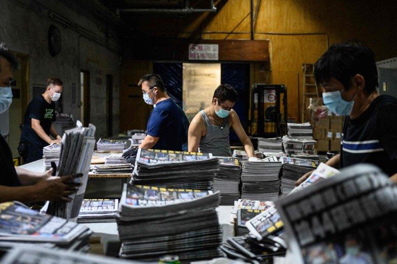 周五,香港《苹果日报》的员工在准备新印刷的报纸。此前一天,警方逮捕了该报的总编辑和四名高管。