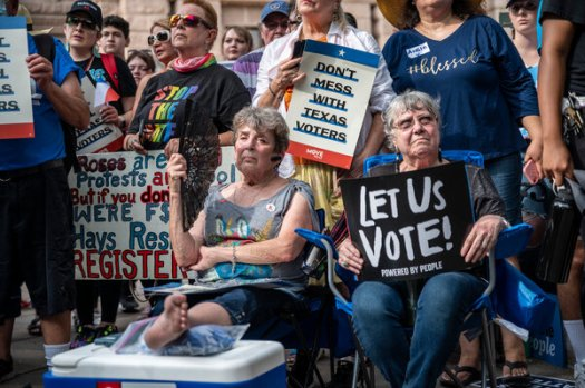 Attendees hold up signs in opposition to a controversial elections bill at a rally this week at the state Capitol in Austin, Texas.