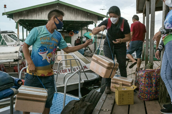 A health care worker loading up protected vials of Covid vaccine bound for hard-hit riverside areas in the Amazon rainforest in northwestern Brazil.