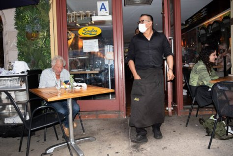 An employee wearing a mask at a restaurant in New York last month while patrons were free to go without face coverings..