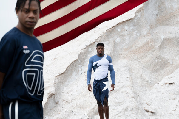 The designer Telfar Clemens, left, and the Olympian Emmanuel Matadi, wearing pieces from the uniform collection Mr. Clemens created for the Liberian Olympic team. These are a sampling of a large collection that will be revealed at the Games.