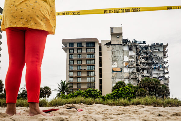 Onlookers surveying the aftermath of a collapsed condominium complex building in Surfside, Fla., a town just north of Miami Beach, Fla., on Thursday.