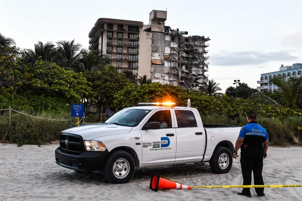 Police stand guard near the partially collapsed building early Thursday in Surfside, Fla.