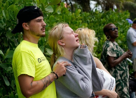 Ariana Hevia, of New Orelans, La., center, near the Champlain Towers South beachfront condo on Friday. Her mother, Cassandra Statton, lived in the building.