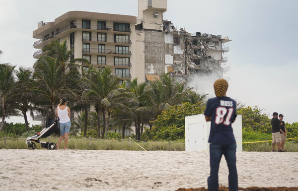 Onlookers at the beach on Friday at the site of the Champlain Towers condominium collapse in Surfside, Fla.