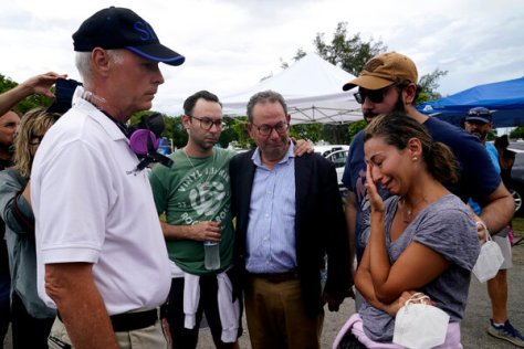 Mayor Charles Burkett of Surfside, Fla., left, talking with Rachel Spiegel, right, who is looking for information on the Champlain Towers South Condo building, on Saturday.