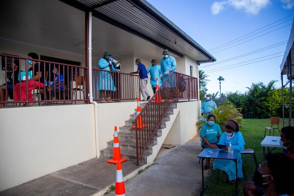A health officer directed residents for coronavirus testing in Suva, Fiji, in June. Daily reports of confirmed Covid cases have rocketed upward in recent weeks.