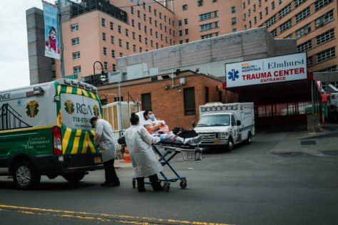 A patient being wheeled on a stretcher to a waiting ambulance outside Elmhurst Hospital in Queens in April 2020.