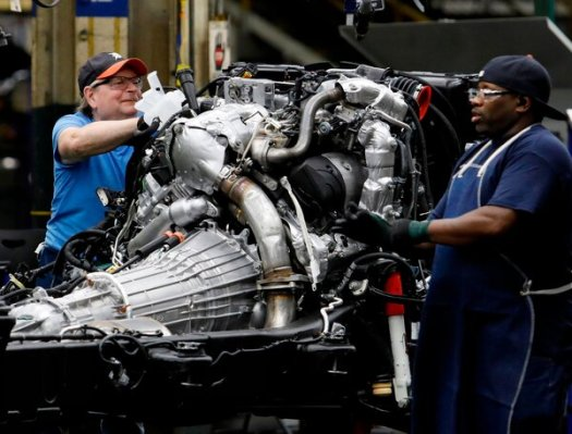Line workers building the chassis of General Motors pickup trucks in Flint, Mich.