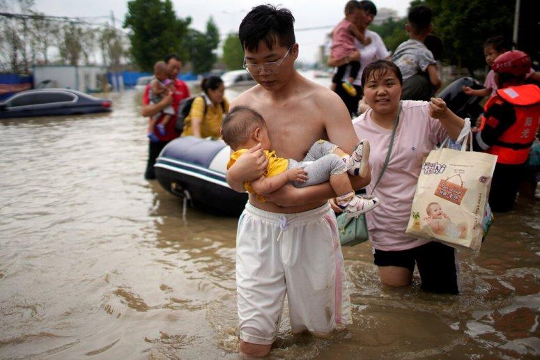 周四,在中国郑州一条被洪水淹没的道路上跋涉的民众。在连续几天的倾盆大雨之后,天气预报称该地区还会有更多降雨。