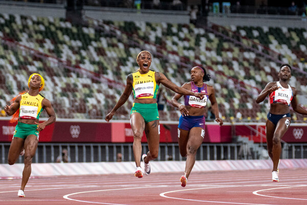 Elaine Thompson-Herah setting an Olympic record while winning the women's 100-meter gold medal.