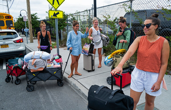 Kristen Pavese, center, and her bridesmaids after departing a ferry in Bay Shore, N.Y., on Saturday. They cut short a bachelorette party weekend on Fire Island because of the storm.