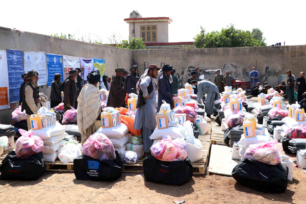 Displaced Afghan families receiving food distributed by the World Food Program in Kandahar last year.